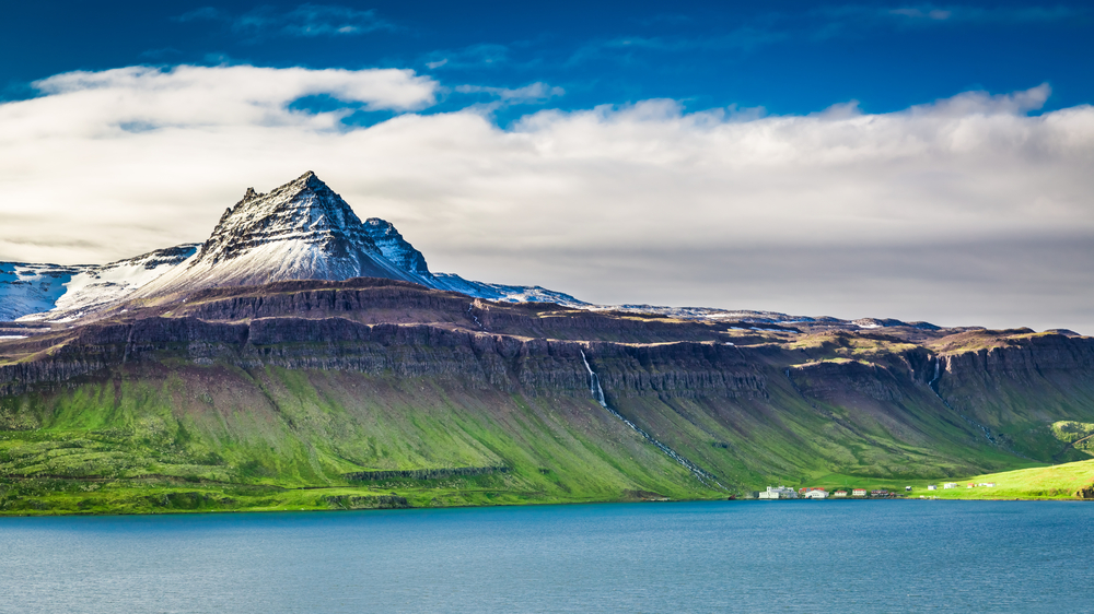 Volcanic mountain over a green fjord during June in Iceland