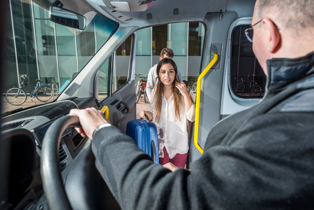 Couple getting on airport shuttle bus to go to Iceland's Blue Lagoon