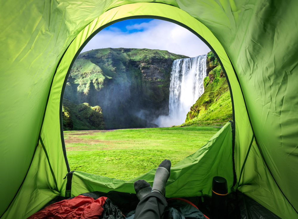 View from green tent of Skogafoss waterfall during summer camping trip