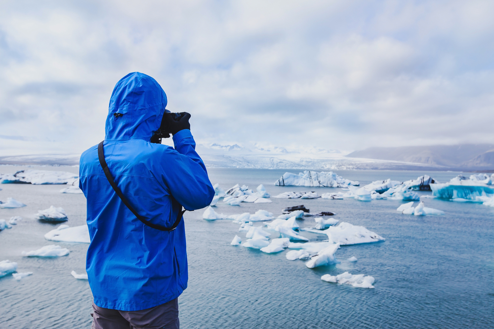 Tourist in blue jacket looking out over Jökulsárlón Glacier Lagoon