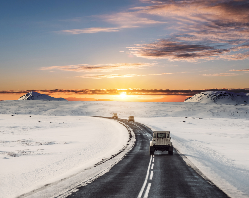Three Icelandic Jeep rentals driving on a snowy road at sunset