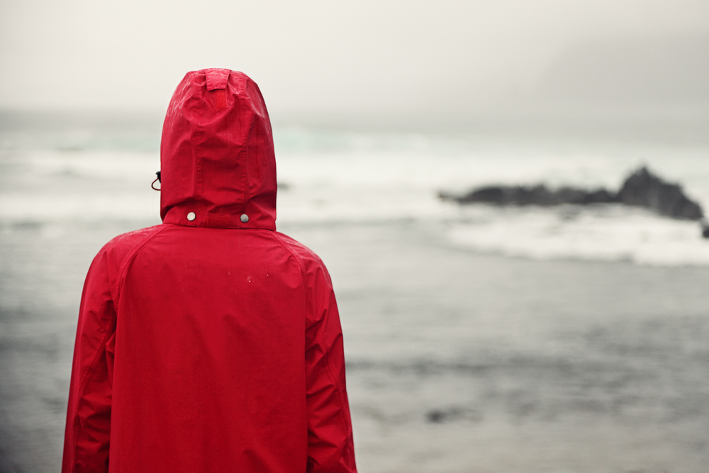 Red rain jacket facing sea during October in Iceland