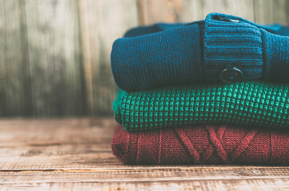 Colorful pile of cozy sweaters to pack for Iceland