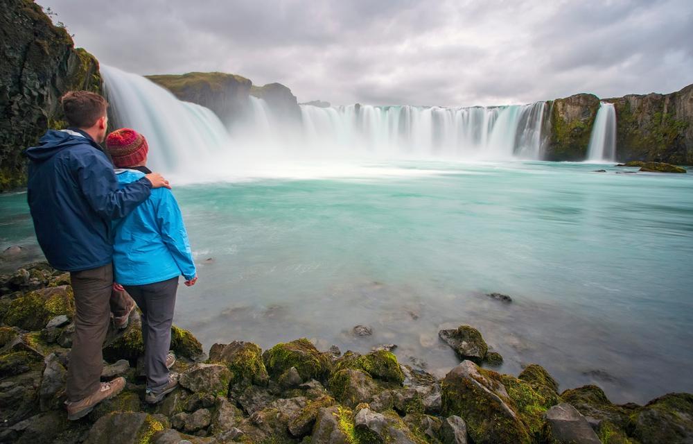 Couple enjoying Godafoss waterfall close to Akureyri in North Iceland