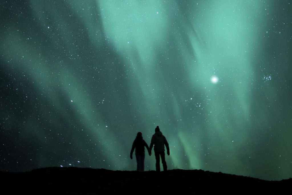 Iceland honeymoon couple watching Northern Lights